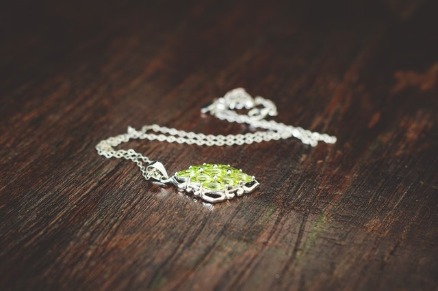 Strieborná retiazka so zelenými kameňmi na drevenom stole.jpg
