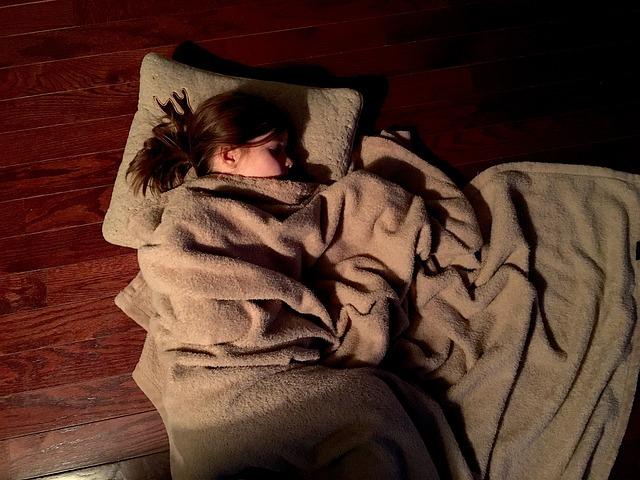 Žena leží prikrytá dekou na podlahe.jpg