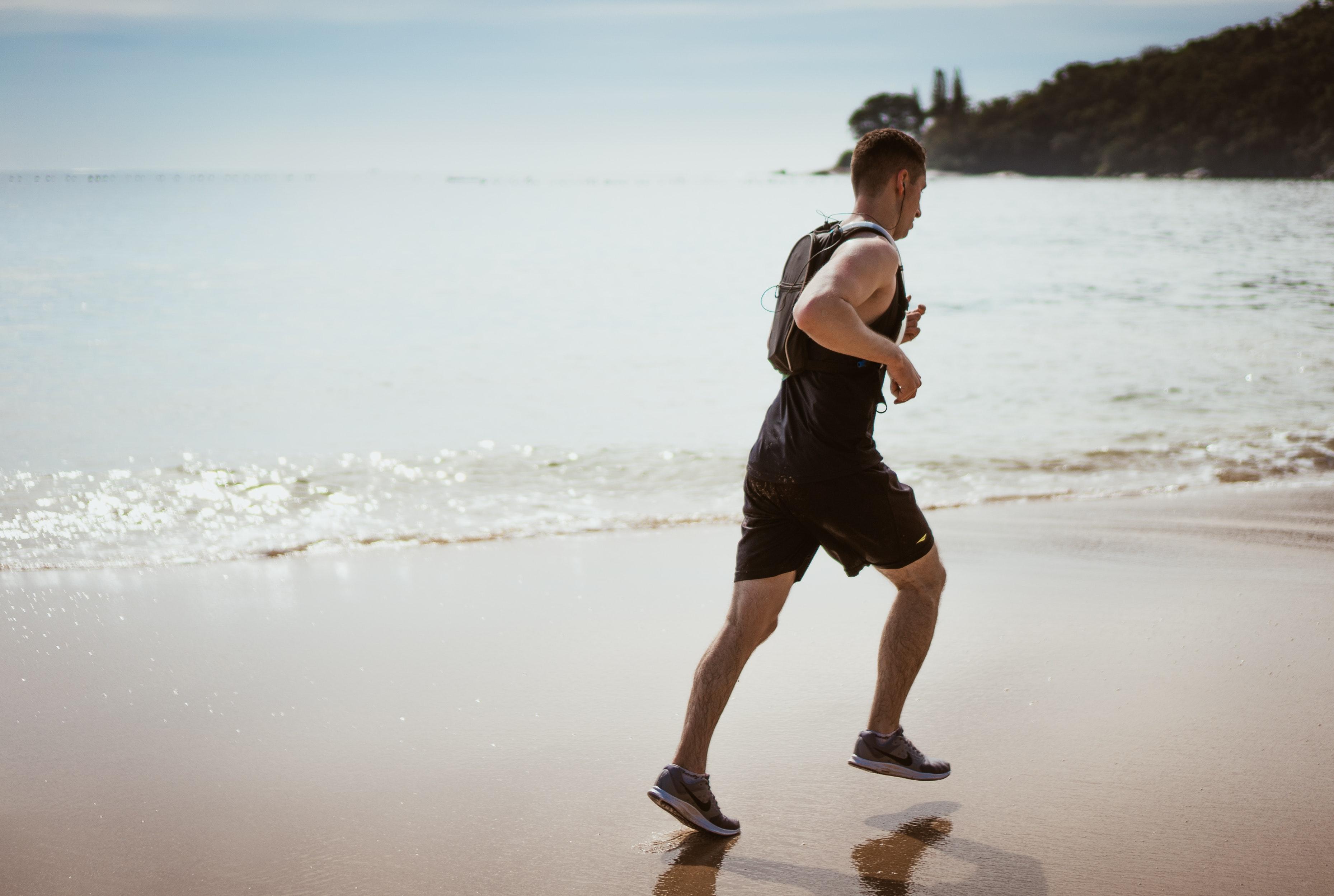 muž beží po pláži