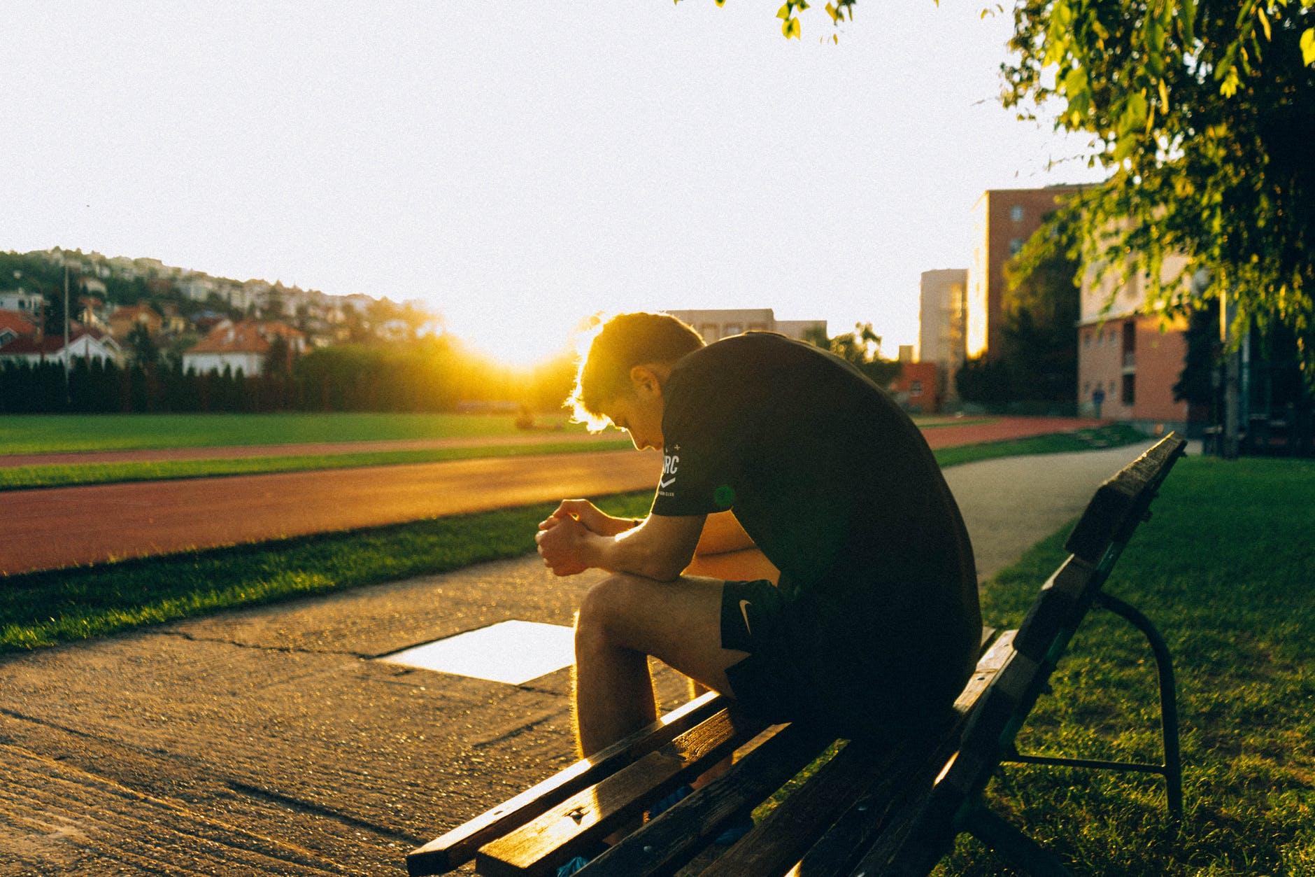 muž sedí na lavičk